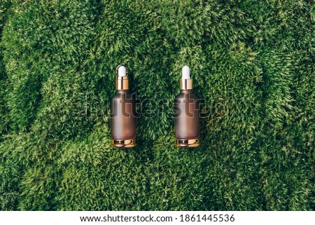 Amber glass cosmetic bottle on green background, natural moss, grass. Skin care, organic body treatment, spa concept. Vegan eco friendly cosmetology product. Biophilia design. Organic cosmetics. Foto stock ©
