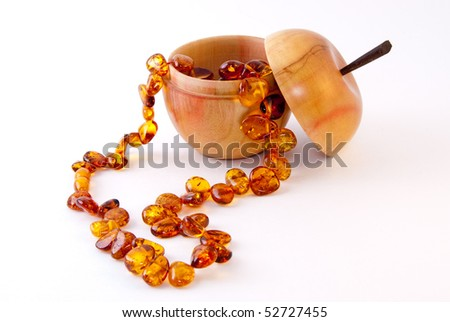 Amber necklace with wooden apple box on white background.