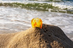 Amber on a sandy beach. One piece of transparent mineral Sunstone on the background of the sea. Ancient resin, processed amber on a sandy beach, blurred background of sea waves in the background. The