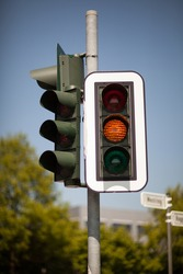 Amber traffic light warning of a progression to a red light bringing trafic to a halt at an intersection
