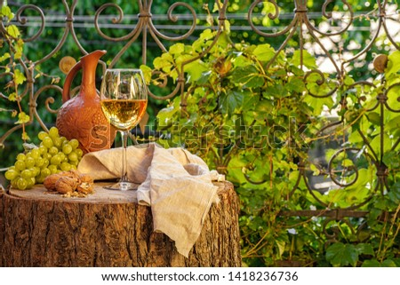 Amber wine in the glass. Georgian national wine according to old technology. Beautiful still life with a drink, fruits and decorations in a rustic style. Copy space. Close up and horizontal view.