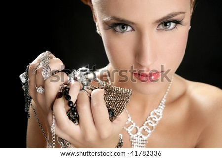 Ambition and greed in fashion woman with jewelry in hands on black background