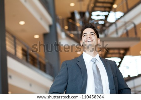 ambitious and optimistic young businessman looking up