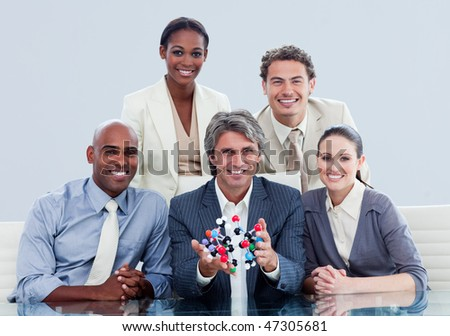 Ambitious business team showing a molecule in a meeting