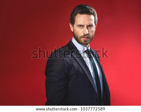 Ambitious businessman. Waist-up portrait of bristled stylish young man is standing and looking at camera seriously. Isolated on red background