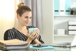 Ambitious businesswoman looks away dreaming sitting drinking coffee at office