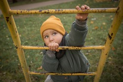 Ambitious, determined, motivated child boy, climbing up yellow ladder in yellow hat, looking up, striving to reach the top, playing outdoors in children playground