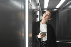 Ambitious employee is waiting the elevator to stop and listening to music in her headphones using smartphone. Female office worker is looking at the floor number in the lift holding gadgets.