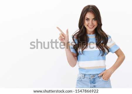 Ambitious gorgeous european woman with curly long hairstyle smiling inspired and thrilled, suggest go check out together awesome new cafe, pointing upper left corner smiling excited stock photo