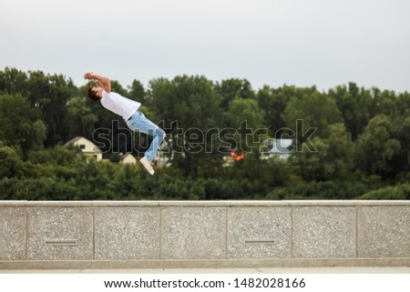ambitious man performing back flip in the street. full length back view photo. spare time, free time . copy space
