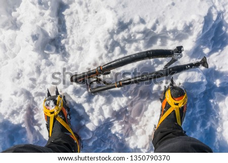 Ambitious winter mountain tourism. Two ice axes stuck in the snow at the foot of the high mountain boots with crampons. View from above. #1350790370