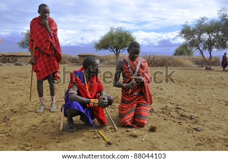 AMBOSELI, KENYA ,OCT. 13: Portrait of young Maasai  warriors showing how they make fire in a traditional way to guests visiting their village taken on Oct 13, 2011 in Masai Mara, Kenya.