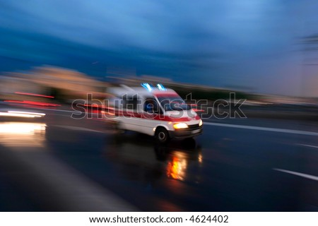 Ambulance car speeding, blurred motion. Deliberately blurred to convey  speed.