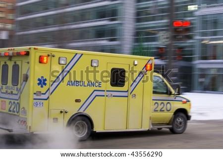 Ambulance car speeding blurred motion in american city on street warning lights flashing dramatic smoke