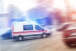 Ambulance racing through city traffic jam on slippery road with slush snow. Car accident on highway