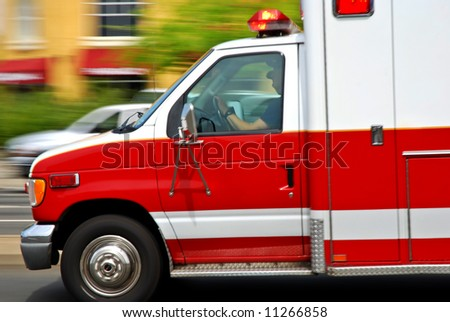 Ambulance speeding down the wrong side of an American street heading to an emergency, motion blur