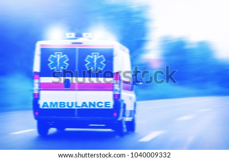 Ambulance van on highway, emergency lights, blurred motion