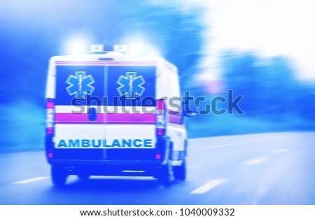 Ambulance van on highway, emergency lights, blurred motion