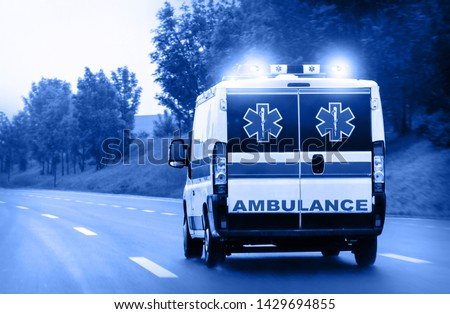 Ambulance van on highway with flashing lights #1429694855