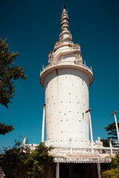 Ambuluwawa multi-religious sanctuary and biodiversity complex.  Large tall tower is stylized from Buddhist stupa, Hindu kovil, Muslim mosque, and Christian church altogether. Tower against clear skies
