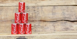 AMELAND DUTCH - 17 APRIL 2017.: COCA COLA. Coca Cola can drinks on wooden background., The carbonated soft drink is produced by The Coca-Cola Company.