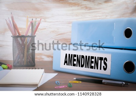 Amendments. Office Binder on Wooden Desk. On the table colored pencils, pen, notebook paper Photo stock ©