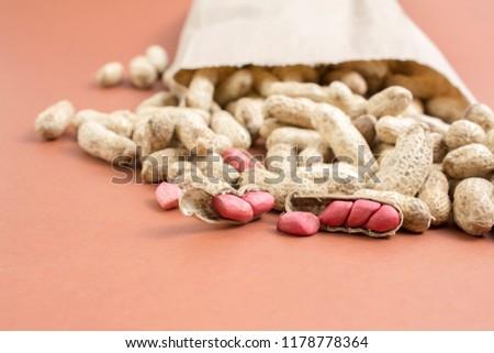 Amendoins abertos saindo do saco de papel Foto stock ©