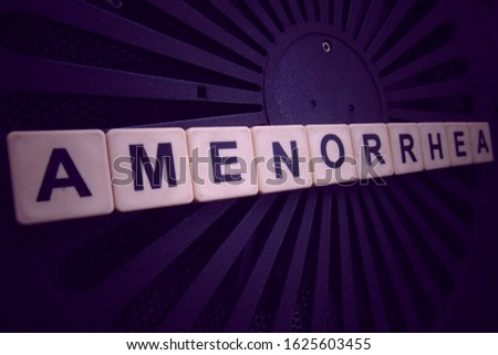 Amenorrhea, word cube with background.