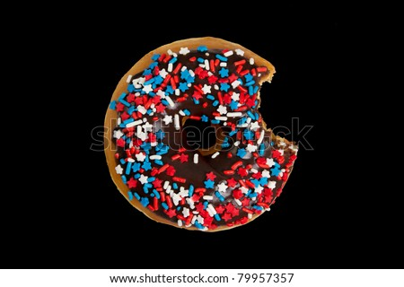 America Themed Donut with Red White and Blue Sprinkles and Stars with Bite Missing Isolated on a Black Background