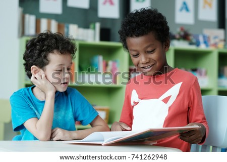 American and african boys are reading and studying together with happiness in their classroom, kid education concept #741262948