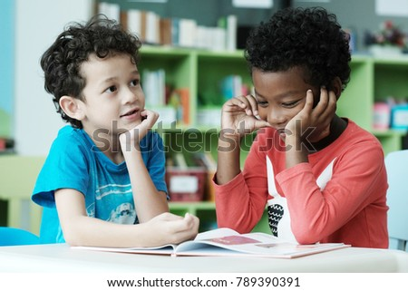 American and African boys are reading and studying together with happiness in their classroom, kid education concept #789390391