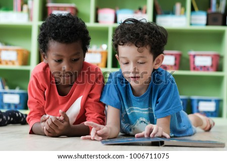 American and African boys are reading together with happiness in their kindergarten classroom, kid education concept