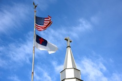 American and Christian flag fly besides a church steeple with a cross symbol on top.  Blue skies and white whispy clouds fill background.