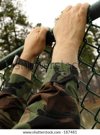american army soldier climbing fence