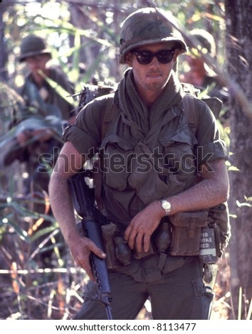 American Army Soldier patrols with an M16 in hand during in 1972. High film grain. - stock photo