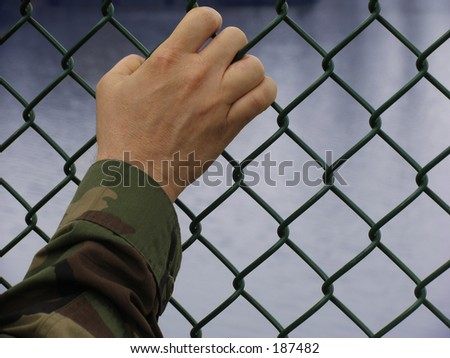 american army soldier's hand on a fence with clipping path