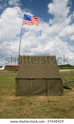 American army tent on the airfield with american flag and fragments of planes behind