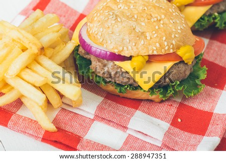 American beef burgers with cheese on the white wooden table. Selective focus and small depth of field.