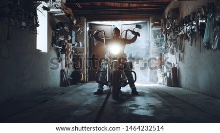 American biker with his motorcycle in the garage. cool and powerful chopper which the biker collected with his own hands Stock photo ©