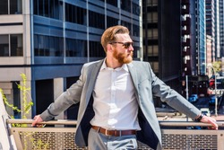 American Business Man with beard, mustache works in New York, wearing cadet blue suit, white shirt, sunglasses, stands by railing on balcony, facing street under sun. Filtered look with blue tint.