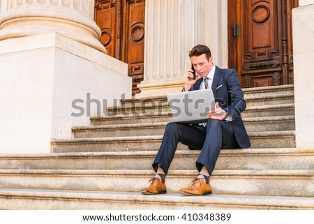 American Businessman traveling, working in New York, dressing in black suit, leather shoes, sitting on stairs outside office, working on laptop computer, calling on phone. Instagram filtered effect.  Сток-фото ©