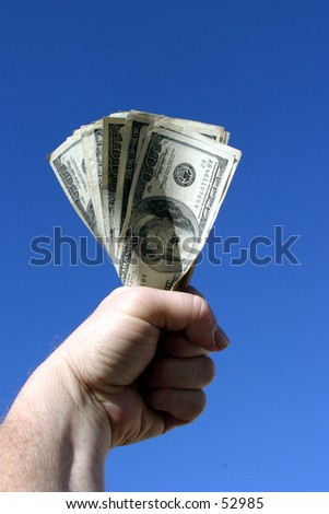 american cash being held tight in the fist of a real humanbeing against a blue sky background