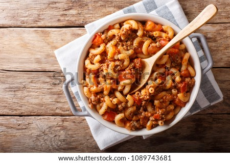 american chop suey, american goulash, with elbow pasta, beef and tomatoes close-up in a saucepan. horizontal top view from above Stock fotó ©