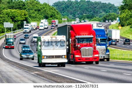 American colors reflect in three trucks leading traffic on an interstate highway. Shot on hot day. Asphalt heat waves cause distortion on vehicles farther from camera, enhancing long telephoto effect.