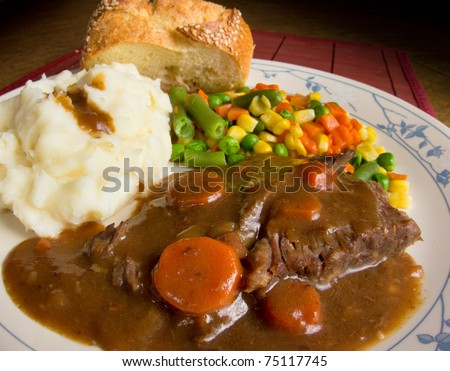 American comfort food; a heart dish of pot roast smothered in gravy, mashed potatoes and mixed vegetables.  This is a dish of real homecooked meat and potatoes.