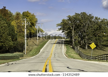American country asphalt road with school bus sign
