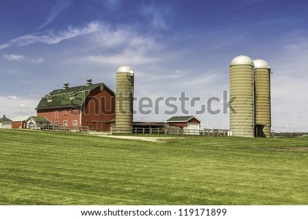American country farm with silos against blue sky