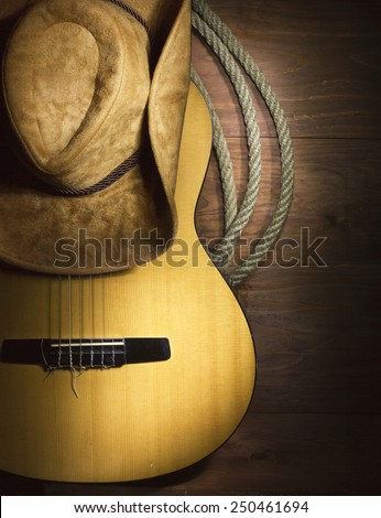 American Country music with guitar and cowboy hat on wood background