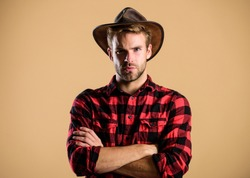 American cowboy. Beauty standard. Example of true masculinity. Cowboy wearing hat. Western life. Man unshaven cowboy beige background. Unshaven guy in cowboy hat. Handsome bearded macho.