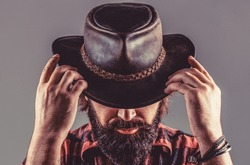 American cowboy. Leather Cowboy Hat. Portrait of young man wearing cowboy hat. Cowboys in hat. Handsome bearded macho. Man unshaven cowboys.